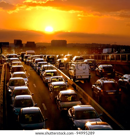 Car traffic against the sunset background. - stock photo