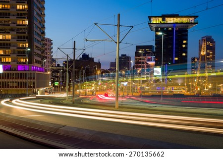 Car traffic driving in and out leaving light trails on the Erasmus bridge in Rotterdam, the Netherlands, at dusk, emphasising the dynamics of this Dutch city - stock photo