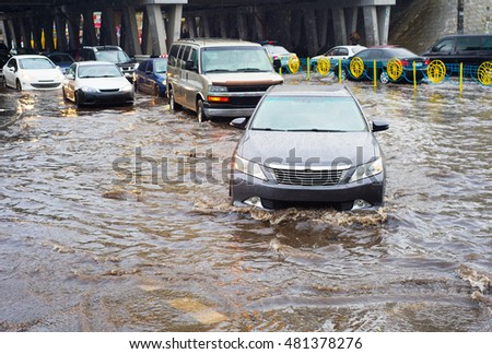 Car traffic in a heavy rain on a flooded city road