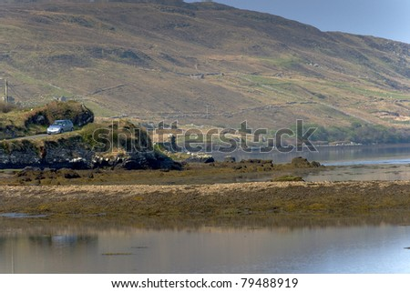 Car travelling though lakside road at Connemara, Ireland - stock photo
