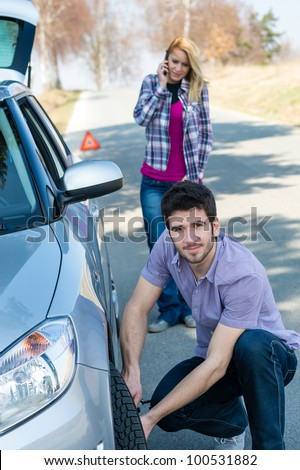 Car wheel defect man change puncture tire woman calling assistance - stock photo