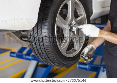 car wheel tire replacement on the scissor cranes by hands of mechanic in the garage - stock photo