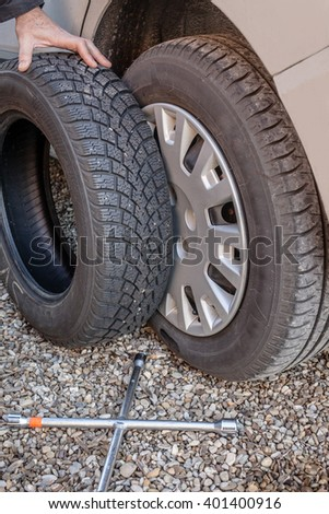 Car wheel with a replacement winter tire on a side and a lug wrench