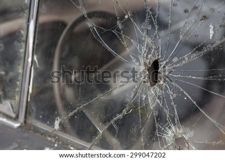 Car window after a raid has a  bullet hole - stock photo