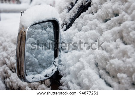 Car wing mirror all covered up with snow, close up image