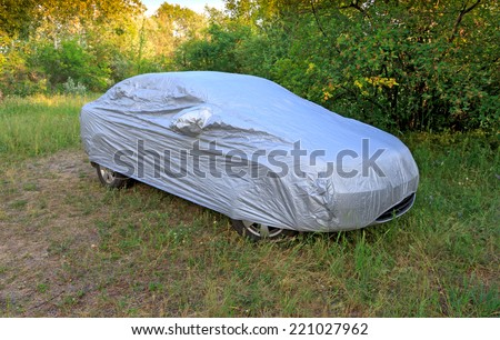 car with cover in forest meadow - stock photo