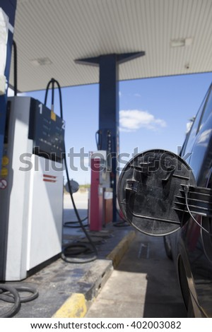 Car with gas cap open ready for refuel on a petrol station - stock photo