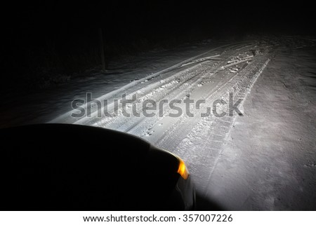 Car with it's headlights on driving through the snow  - stock photo
