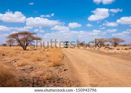 Car with people in the African desert - stock photo