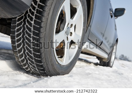 Car with winter tyres installed on light alloy wheels in snowy outdoors road - stock photo