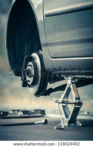 Car without tire on the road - stock photo