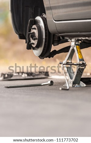 Car without tire on the road need to be repaired - stock photo