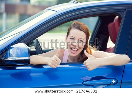 Car. Woman driver happy smiling showing thumbs up coming out of blue car side window on outside parking lot background. Beautiful young woman happy with her new vehicle. Positive face expression - stock photo