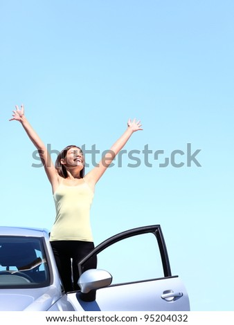 Car woman happy freedom concept. Cheering young woman with arms raised stepping out of new car under blue sky. Beautiful young multiracial Asian / Caucasian female model free. - stock photo