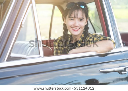 Car woman happy in old  retro vintage car. Young woman driving on road trip on beautiful sunny summer day. Pretty mixed race Asian / Caucasian female model.