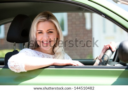 Car woman happy in small green car. Attractive young woman driving on road trip on sunny summer day - stock photo