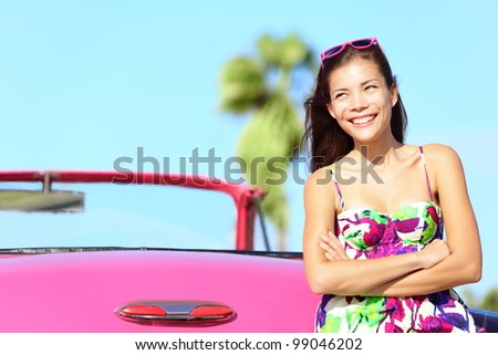 Car woman happy smiling by pink vintage car. Beautiful young multiracial female driver in Havana, Cuba.
