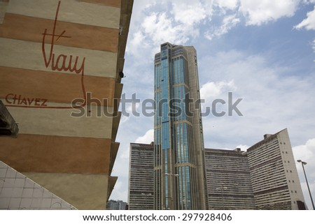 CARACAS, VENEZUELA, APRIL 20: Downtown of Caracas with view on hight residential buildings, the official signature of President Hugo Chavez is also visible on a wall in the foreground. Venezuela 2015 - stock photo