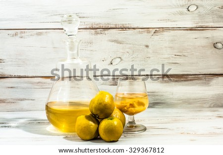 Carafe and glass of alcohol tincture for drink with quince fruits. - stock photo