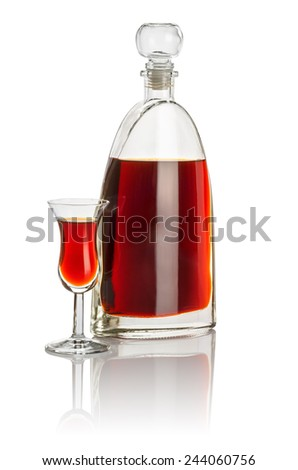 Carafe and high stem glass filled with brown liquid - stock photo