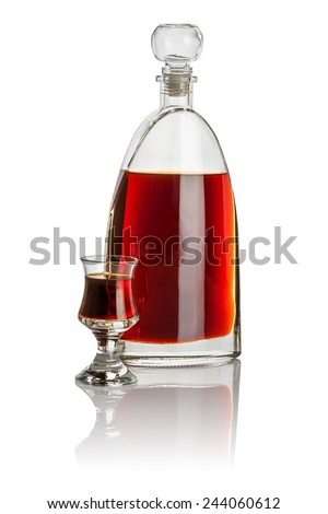 Carafe and schnapps glass filled with brown liquid - stock photo