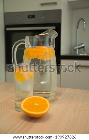 Carafe of water with orange on the kitchen table
