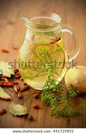 carafe with oil and spices like bay leaf chili and onion on wooden table. - stock photo