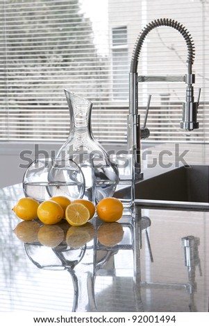 carafes of water and lemons in modern kitchen - freshness - stock photo