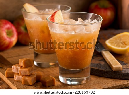 Caramel Apple Cider Cocktails on a rustic background with apples, caramels, and lemon. - stock photo
