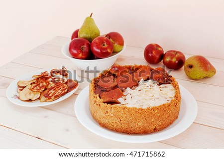Caramel cheesecake with apple and almond petals on a white wooden background top view.