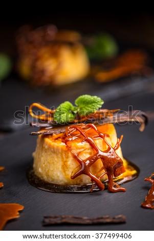 Caramel custard served on black slate - stock photo