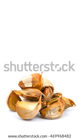 Caramelized cloves of black garlic over white background