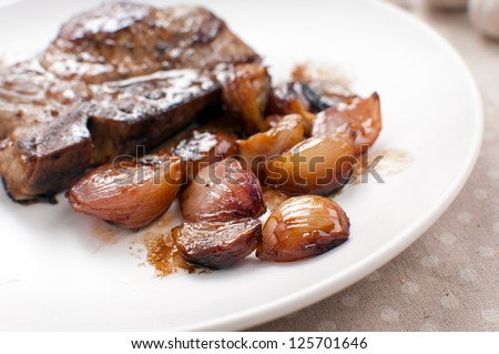 Caramelized garlic and shallots onions with meat closeup - stock photo