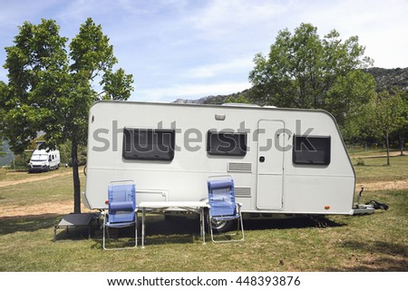 Caravan at a camping with two camping chairs in front