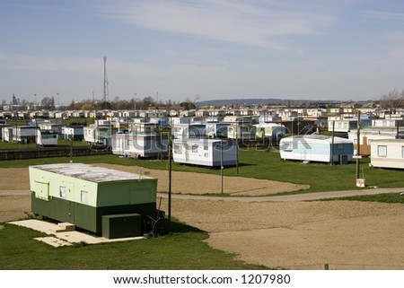 Caravan Park with telephone transmitter in the distance. Old Green caravan in foreground. - stock photo