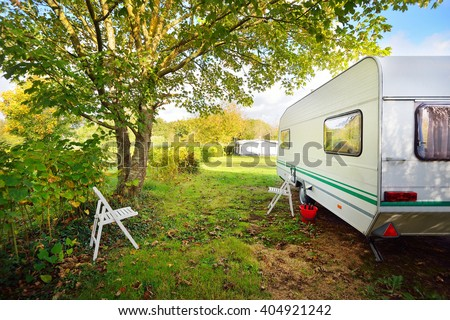 Caravan trailer on a green lawn under the trees, on a sunny Autumn day. France - stock photo