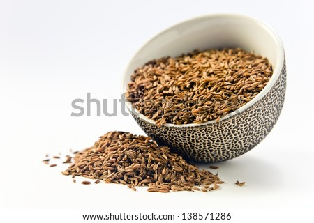 Caraway seeds in a small ceramic cup on a white background - stock photo