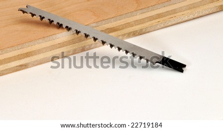 carbide jig saw blade leaning on a piece of plywood - stock photo