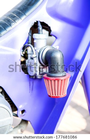 Carburetor and air-filter of small, one-cylinder racing motorbike.Parts of a motorcycle engine tuning. - stock photo