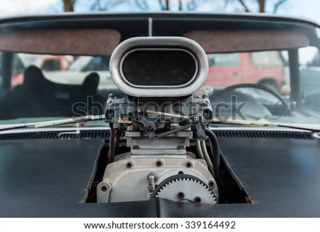 Carburetor on a black V8 car with the hood been cut out for it. - stock photo