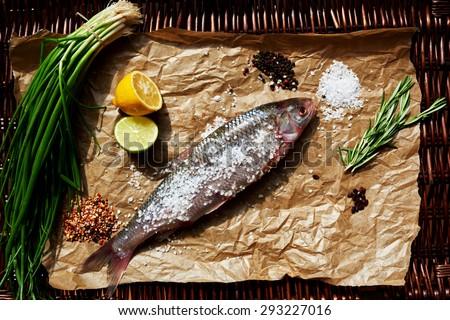 Carcass cook sea bass sprinkled coarse sea salt, lie next to slices of lemon, herbs - stock photo