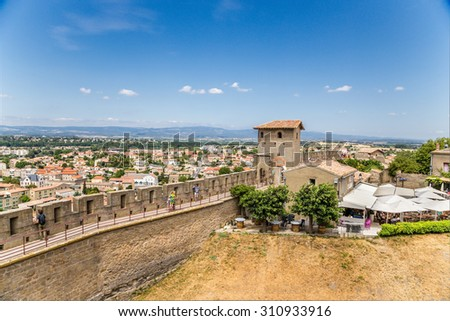 CARCASSONNE, FRANCE - JUL 19, 2015:   Landscape with a fortified wall, medieval tower and a view of the lower city