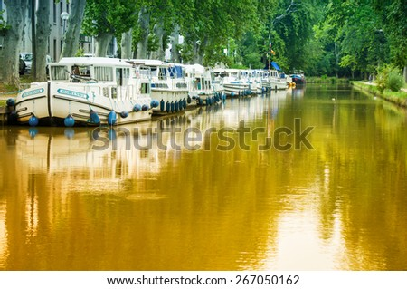 CARCASSONNE,FRANCE - JULY  25: boats anchored at the famous Canal du Midi  on July 25, 2014 in Carcassonne, France. The Canal is a 241 km (150 mi) long canal in Southern France. - stock photo