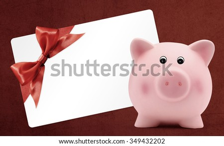 card gift with piggy bank, red ribbon bow, Isolated on red background