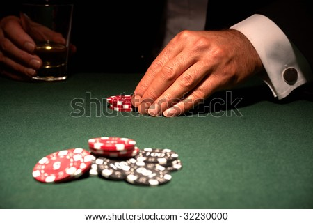 Card player in casino with chips and drink - stock photo