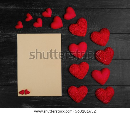 Card to Valentine's Day. Paper for text congratulations letter. Heart from red marzipan. Heart with pattern and heart sleek black wooden background.Top view. Flat lay
