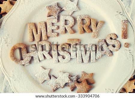 Card with Gingerbread Cookies on Vintage Plate. Baked Letters Merry Christmas and Figures Stars with Powered Sugar. Toned - stock photo