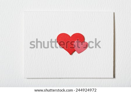 Card with hand crafted red and pink hearts on white paper background - stock photo