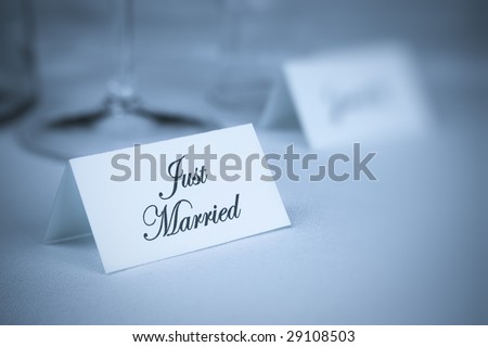 Card with inscription Just Married on table. Shallow DOF. Blue tone. - stock photo