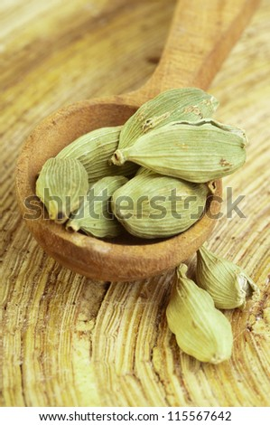 Cardamom pods on wooden spoon